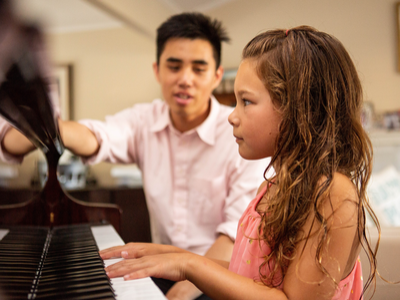 little girl learning how to play the piano during music lessons